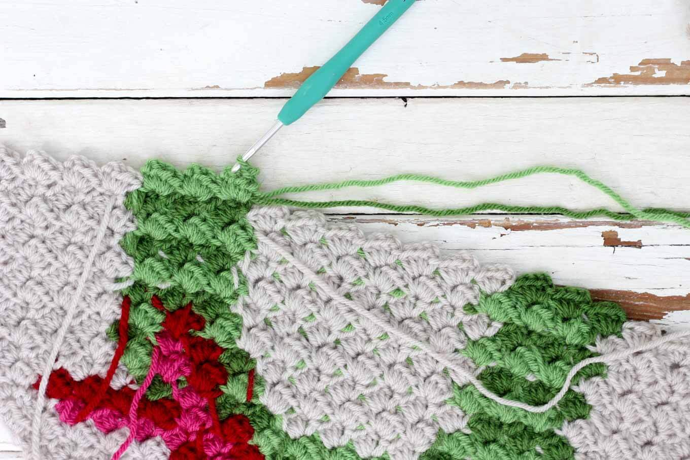 "The final corner to corner Christmas crochet pattern in this nine square series is a modern, monochromatic holiday wreath. Crochet all the squares for a festive Christmas c2c crochet afghan or choose your favorites to make throw pillows! Made with Lion Brand Vanna's Choice in ""Kelly Green,"" ""Fern,"" ""Scarlet,"" ""Cranberry"" and ""Linen."""