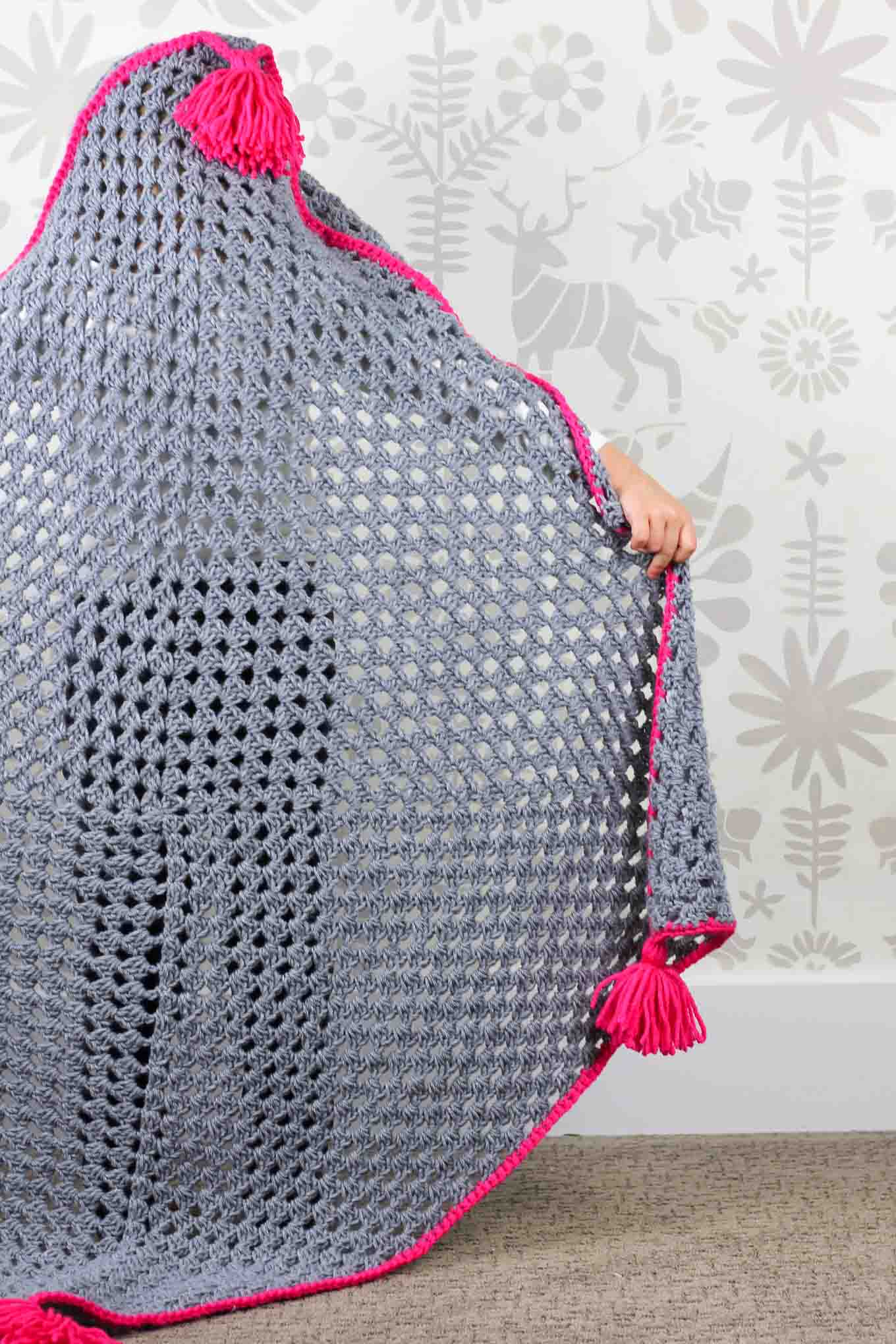 "Based on a large granny square, the ""Granny Gives Back"" crochet hooded blanket pattern makes an easy and inexpensive project to donate to children's charities. The oversized hood and playful tassels will give any kid a safe, warm place to escape to. Click for the free granny square afghan pattern using Lion Brand Pound of Love yarn!"