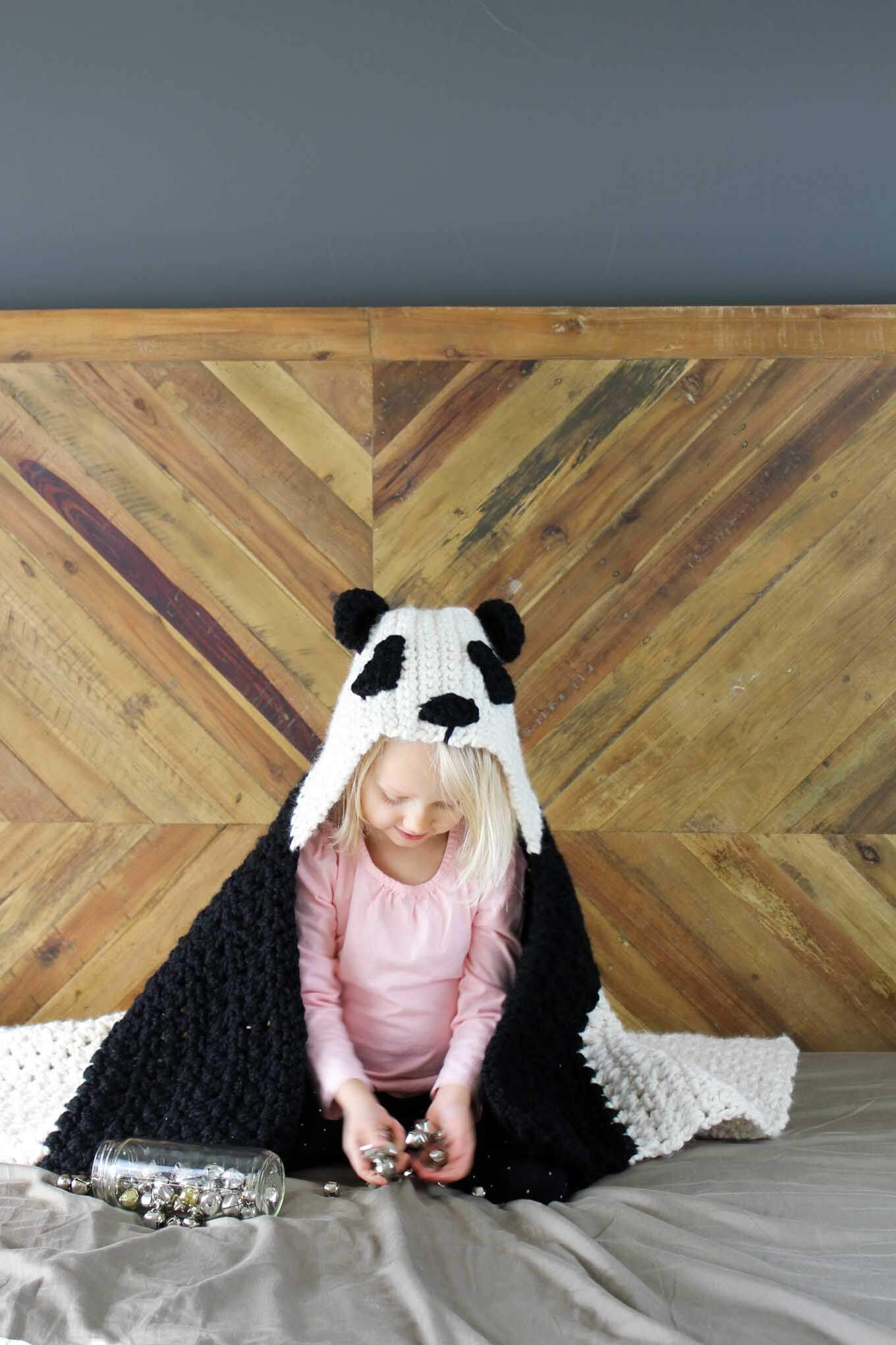 "This free crochet hooded baby afghan pattern will give your favorite child the chance to feel like a cozy little panda. Make one for the new baby to grow into and another for an older sibling to enjoy right away! Customize the pattern to make a crochet koala or polar bear too! Made with Lion Brand Wool Ease Thick & Quick in ""Fisherman"" and ""Black."" Click for the free crochet pattern!"