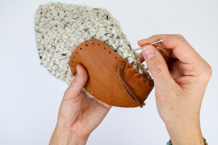 How to add leather soles to crochet or knit slippers. Free slipper soles template from MakeAndDoCrew.com.