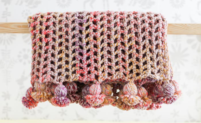 "This pom pom blanket is a 4.5 hour afghan pattern using Lion Brand Wool-Ease Thick & Quick Bonus Bundle in the color ""Spice Market."" Free pattern from Make & Do Crew."