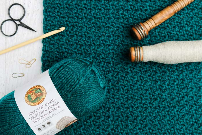 "Lion Brand Touch of Alpaca yarn in the color ""Jade"" with vintage spools of yarn and a wooden crochet hook. The crochet stitch pictured is the Griddle Stitch."