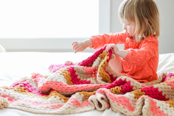 This modern crochet granny stitch baby blanket uses bold stripes and cheerful tassels to create a look that's perfect for kids' rooms and living rooms alike.