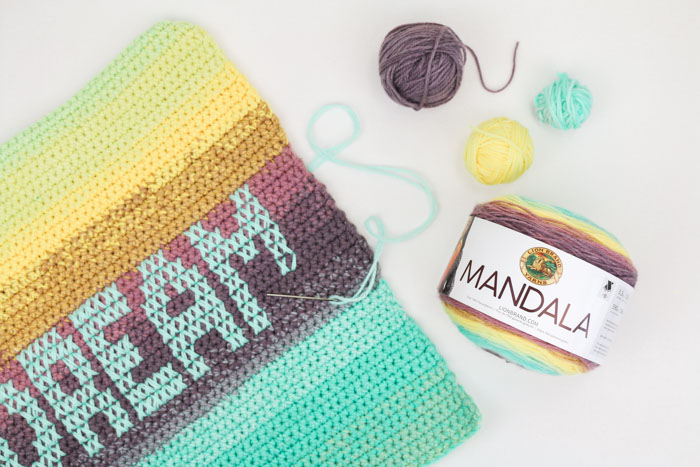 Paint your perfect palette with this ombre pillows made from gorgeous Lion Brand Mandala yarn cakes. Three strands held together throughout creates a chunkier look while the cross stitch detailing allows you to personalize a message for everyone you know.