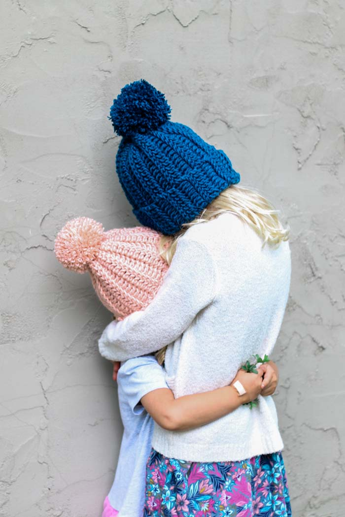 Easy child's crochet hat pattern with a pom pom on two kids hugging. Free pattern and tutorial for children, women and men.
