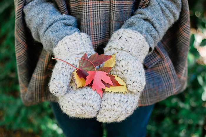 Chunky crochet wool mittens holding orange, yellow and red fall leaves. Free easy pattern and tutorial.