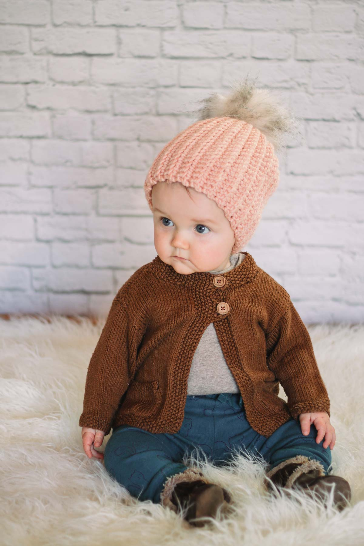 Young baby wearing a handmade crochet hat with a fur pom pom on top.