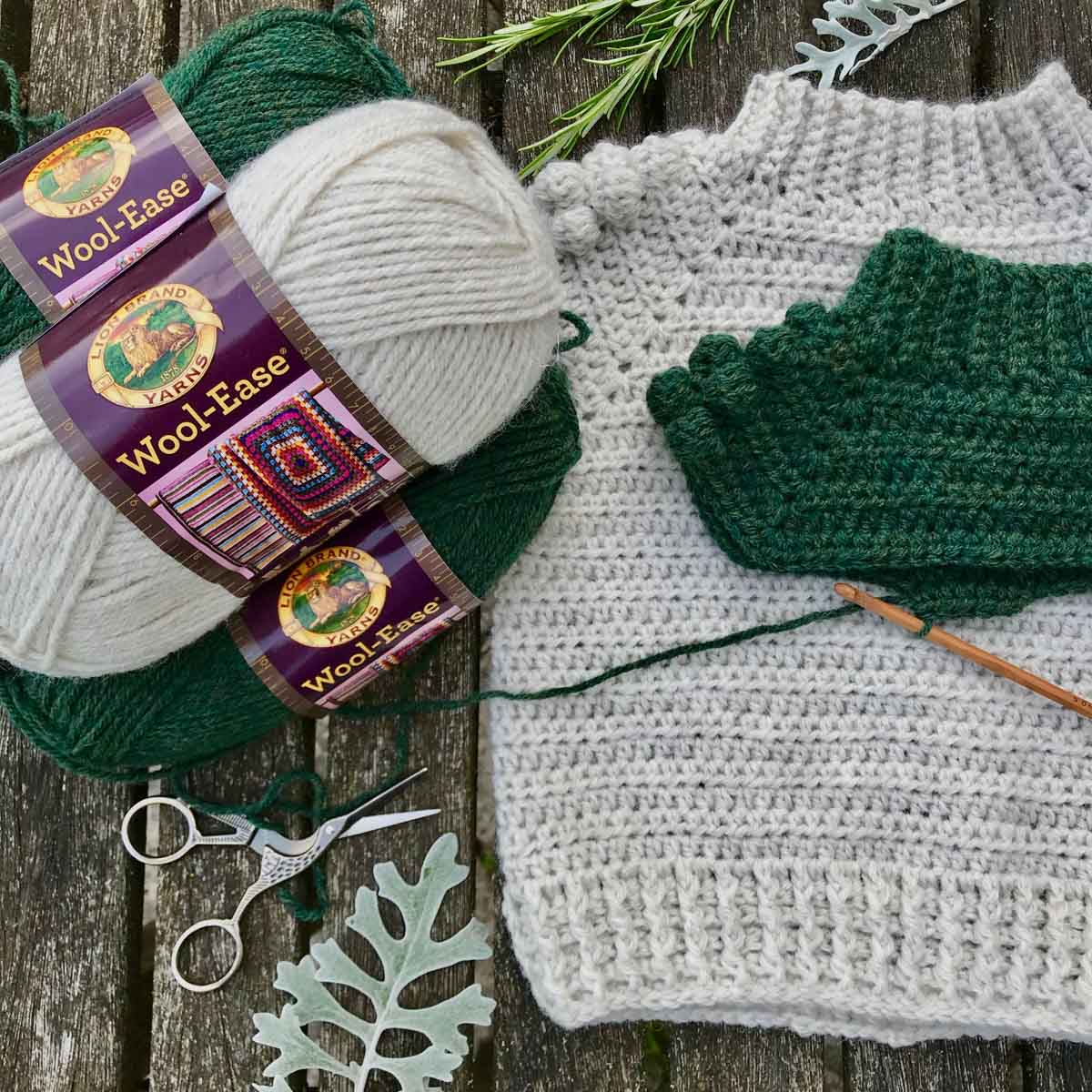 Free crochet pattern for a children's pullover sweater made with Lion Brand Wool-Ease yarn in colors Natural Heather and Forest Green Heather.