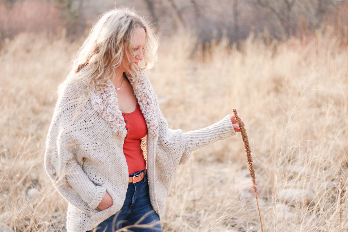 A woman in a field with her hand in the pocket of her crochet cardigan made with the Herringbone Double Crochet stitch.