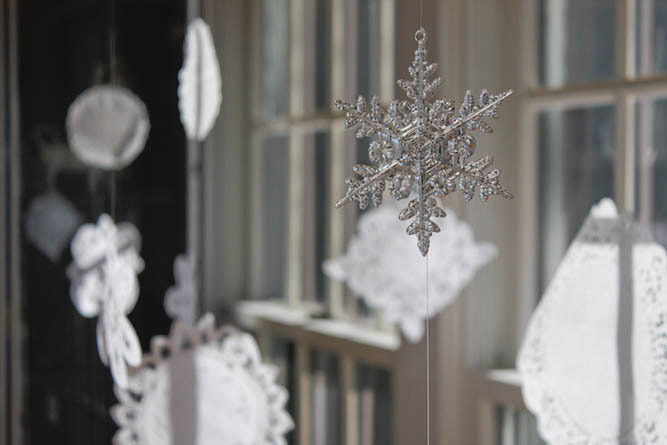 DIY Christmas decor idea--simple doily snowflakes. Perfect simple craft project to do with kids. | MakeAndDoCrew.com