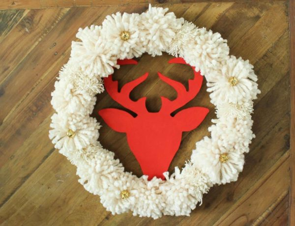 DIY Christmas wreaths are the best! The idea for this DIY Christmas wreath was inspired by a Pottery Barn wreath that costs $129! The DIY version takes less than an hour and is made using a wooden wreath form, DIY pom poms and some jingle bells. Click to view the full step-by-step tutorial. | MakeAndDoCrew.com