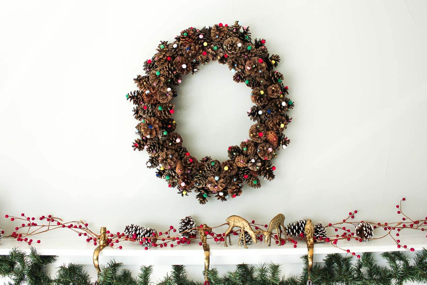 This DIY pinecone wreath is made with adorable little pom poms and costs less than $6 total! Perfect for the Christmas season and beyond. Click to view the full tutorial. | MakeAndDoCrew.com