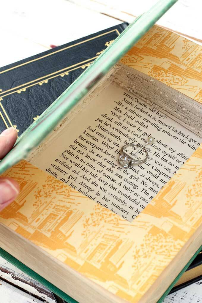 Turn an old vintage book into an keepsake DIY gift box with this simple tutorial. These gift boxes are a creative DIY ring bearer pillow alternative, too! Perfect gift wrap idea for gifts for him, weddings, bridesmaids, Christmas, Valentine's day and a book-lover's birthday. | MakeAndDoCrew.com
