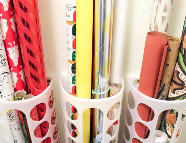 Create simple DIY wrapping paper storage idea using Ikea's Variera plastic bag dispensers. Get those crazy rolls of gift wrap up off the floor and contained in a tidy system! Click for details on measuring and hanging. | MakeAndDoCrew.com