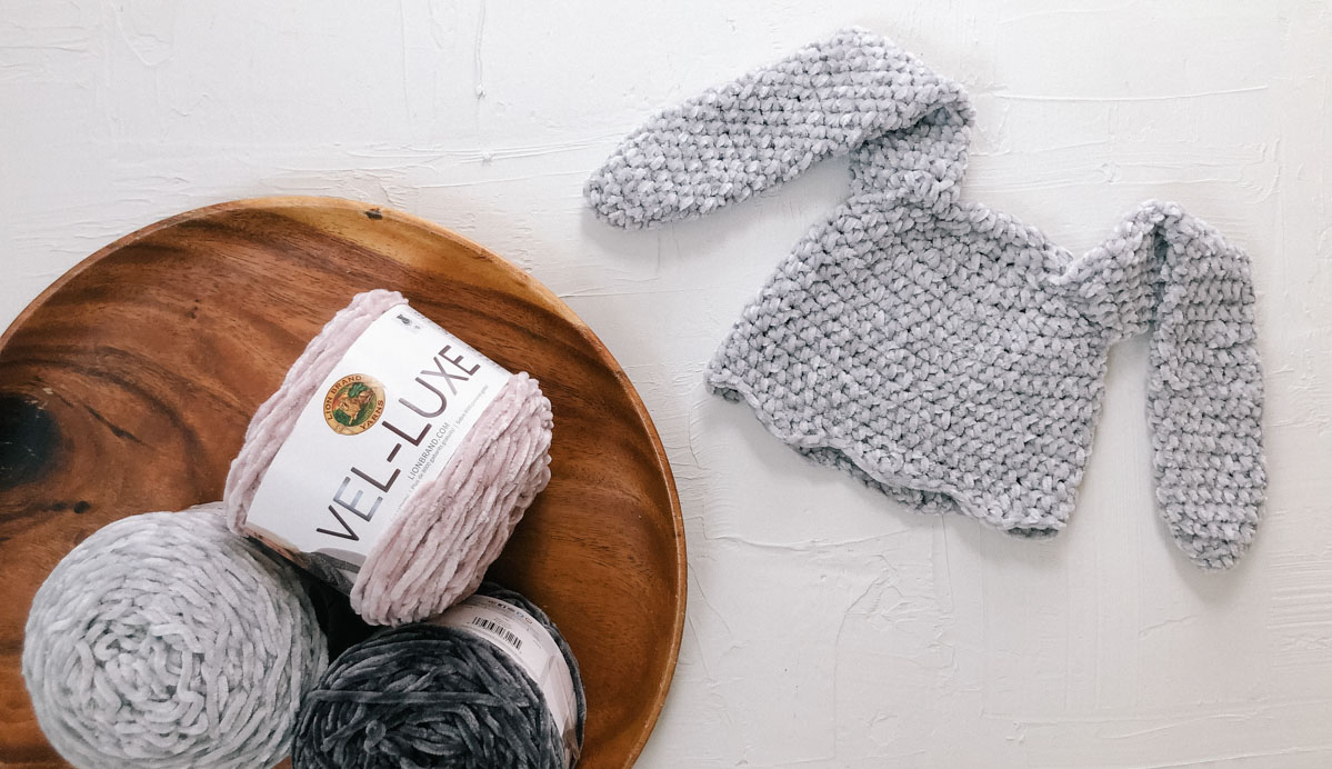 """A crochet bunny hat with long floppy ears crocheted with Lion Brand Veluxe yarn in the color """"Silver""""."""