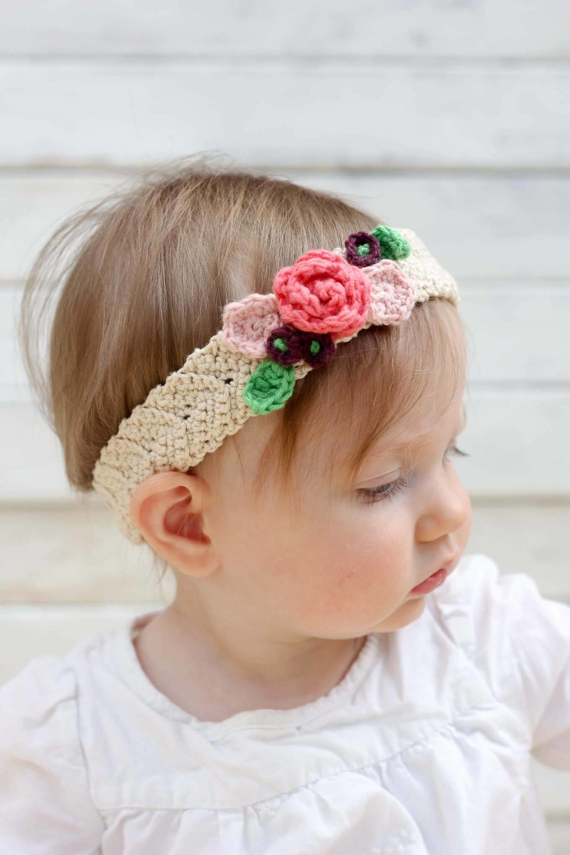 This free crochet headband pattern with flowers is surprisingly easy and it makes an adorable headpiece for a young flower girl in a wedding (or a bohemian beauty of any age)! Sizes include newborn, baby, toddler, child, teen and adult. | MakeAndDoCrew.com