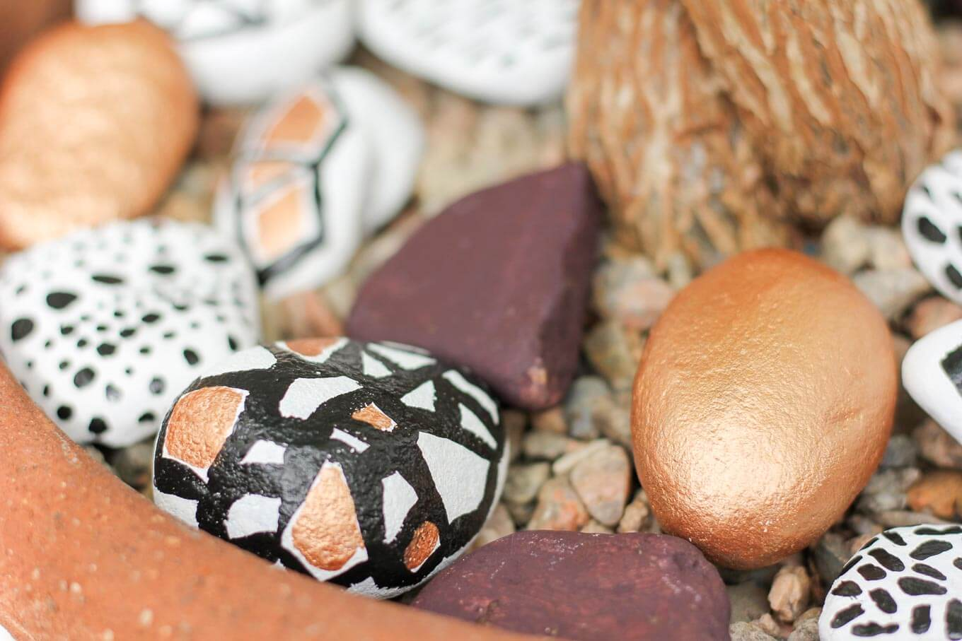 These DIY painted rocks are a simple and budget-friendly craft that add pizazz to potted plants and gardens. Find some stones, grab your paint and dream up some designs! | MakeAndDoCrew.com