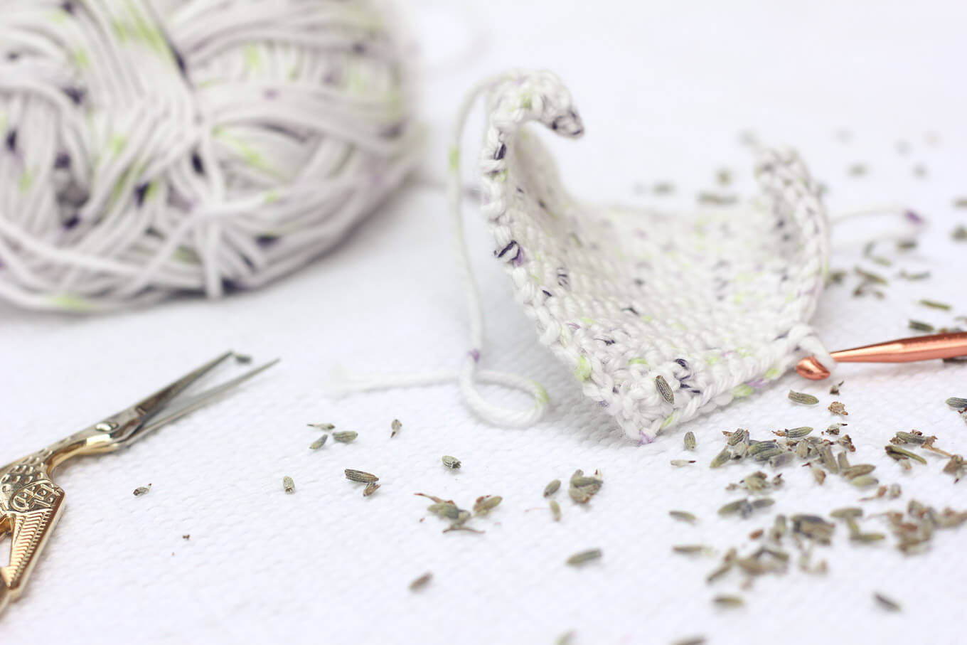 This free crochet pattern is perfect for beginners and a great way to use up dried lavender from your garden! Pop one of these crochet lavender sachets in the dryer and you've got natural and inexpensive way to keep your laundry smelling fresh! | MakeAndDoCrew.com
