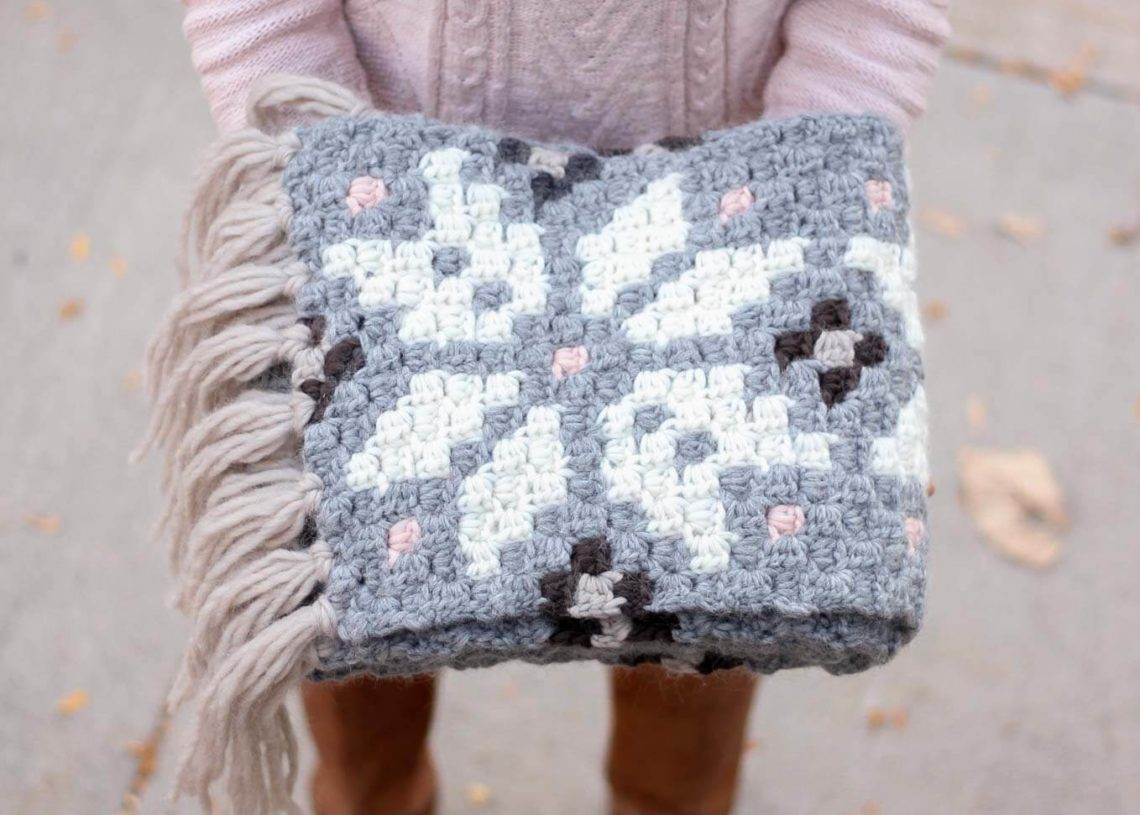 Intarsia crochet pattern that uses repeating modern snowflakes to form a nordic design. Free super scarf pattern!