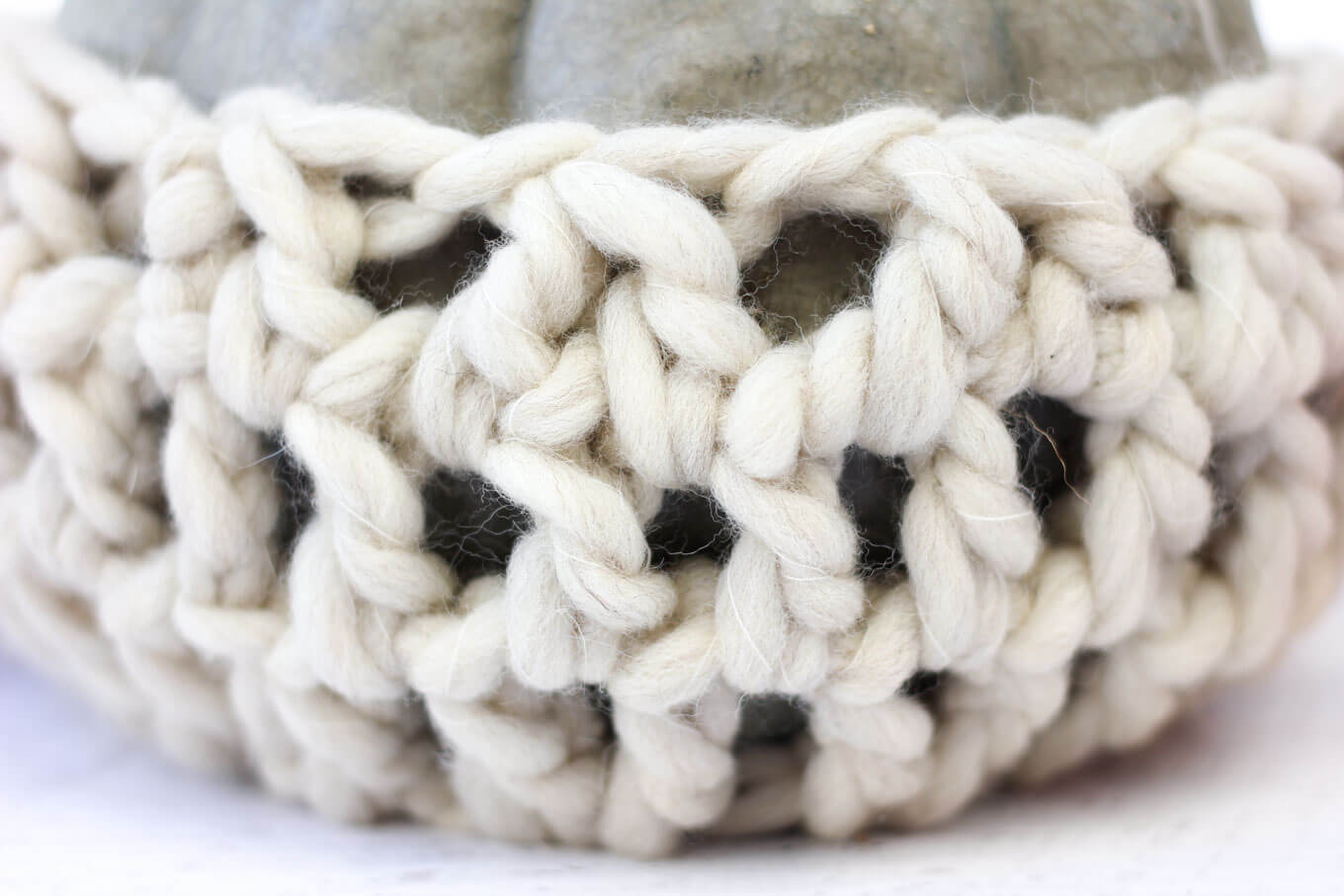 Rich texture of double crochet stitches in natural wool.