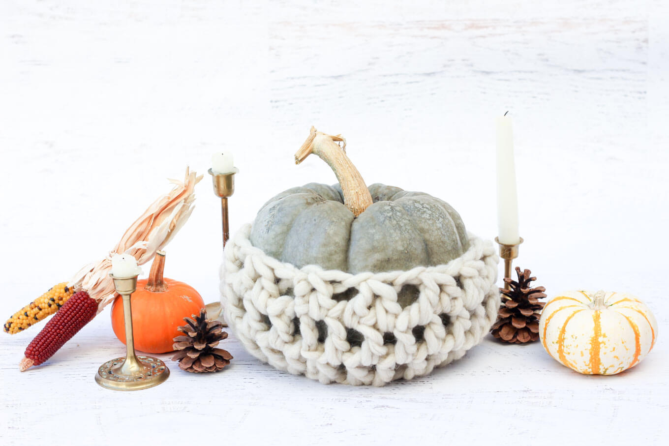 Thanksgiving table decor idea using pumpkins, wool, pinecones and brass candlesticks.