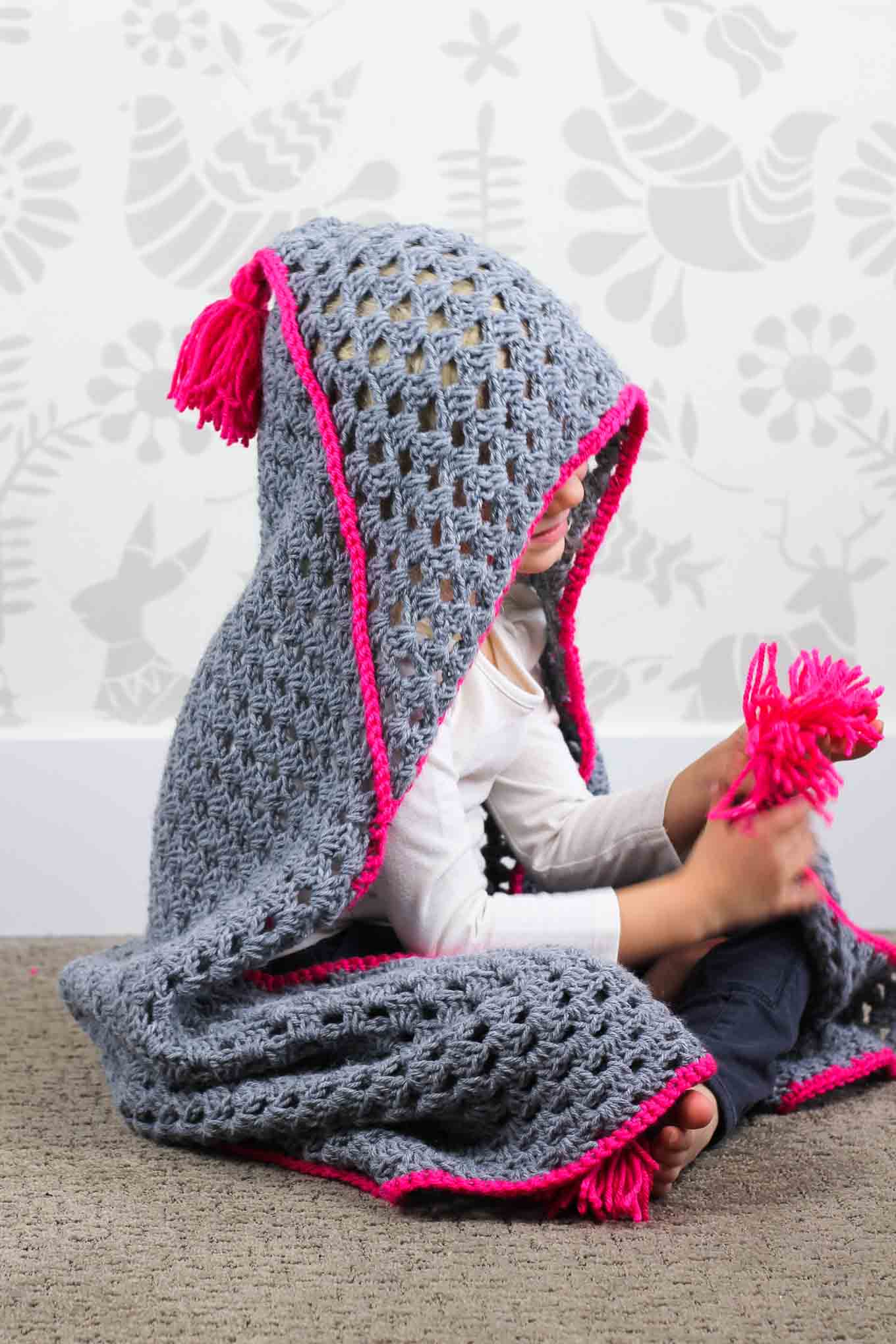 "Based on a large granny square, the ""Granny Gives Back"" crochet hooded blanket pattern makes an easy and inexpensive project to donate to children's charities. The oversized hood and playful tassels will give any kid a safe, warm place to escape to. Click for the free pattern using Lion Brand Pound of Love yarn!"