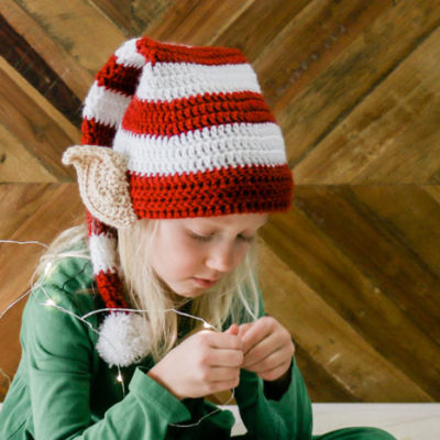 This free Santa's helper crochet elf hat pattern with ears makes a perfect creative family Christmas photo idea! Free pattern and tutorial in sizes newborn, baby, toddler, child, tween and adult. Featuring Lion Brand Vanna's Choice.
