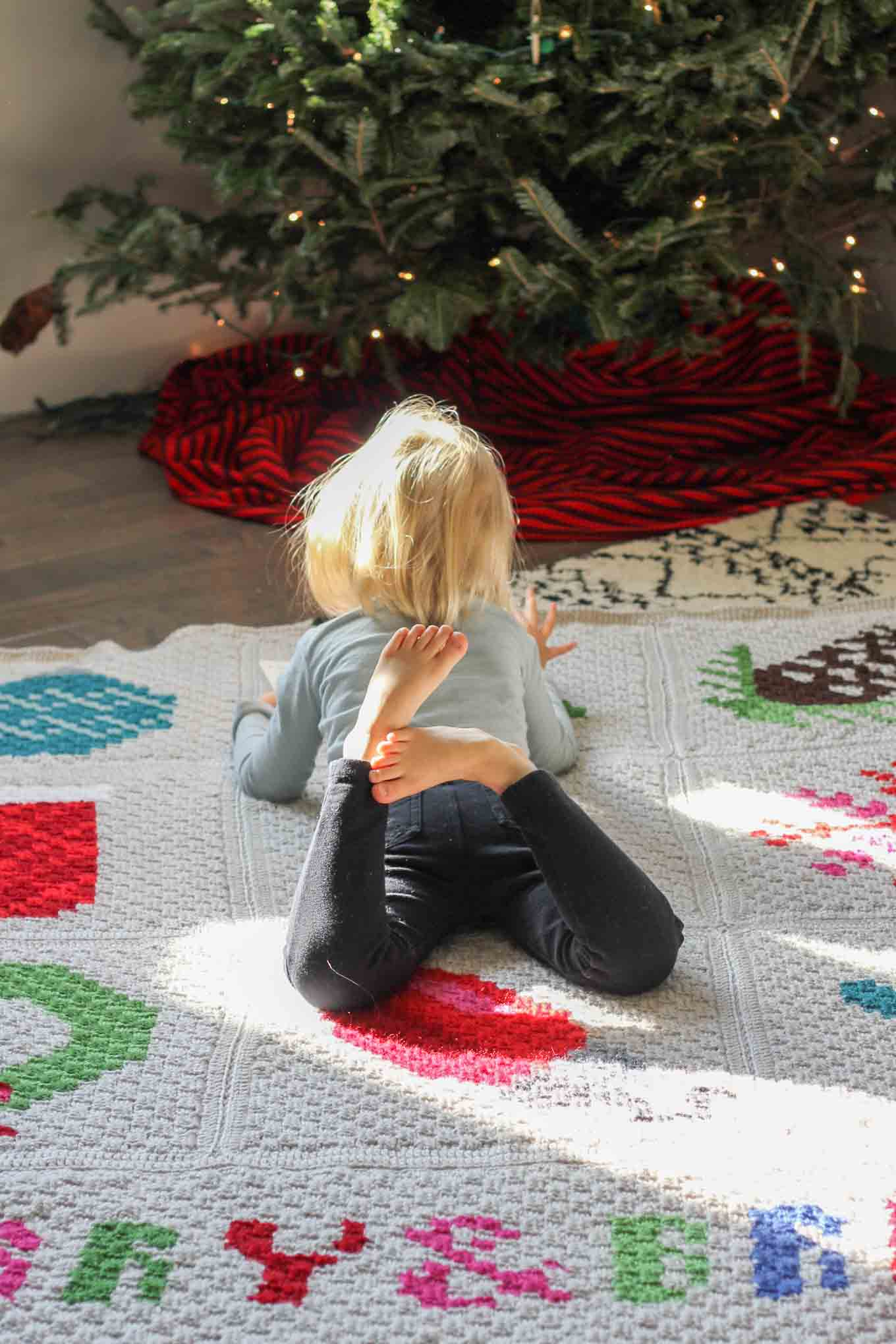 Make an heirloom your family can snuggle up with year after year with this free corner to corner crochet Christmas afghan pattern! These modern c2c Christmas graphs make perfect winter pillows too. Crocheted with Lion Brand Vanna's Choice yarn.