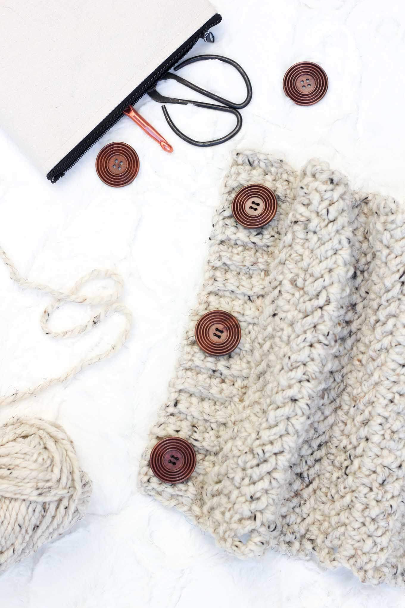 "This free crochet cowl pattern uses the herringbone double crochet stitch to create a deliciously chunky scarf with a modern look! The oversized buttons add another element that is endlessly customizable. Pictured in Lion Brand Wool-Ease Thick & Quick in ""Oatmeal."""