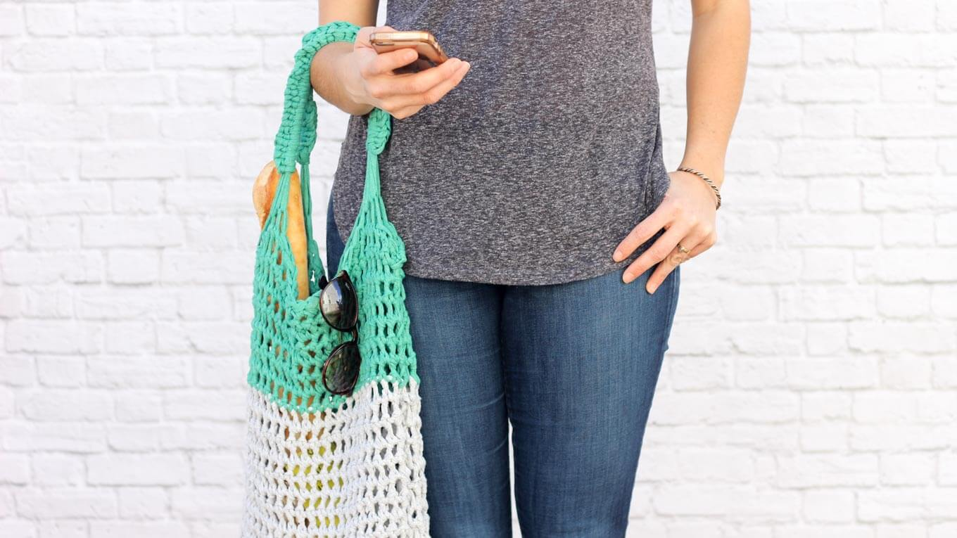 "This free market tote bag pattern and video tutorial is the perfect introduction on how to arm crochet! A speedy, satisfying project for adults and kids alike. Made using Lion Brand's Fast-Track yarn in ""Chopper Grey"" and ""Go Kart Green."" 