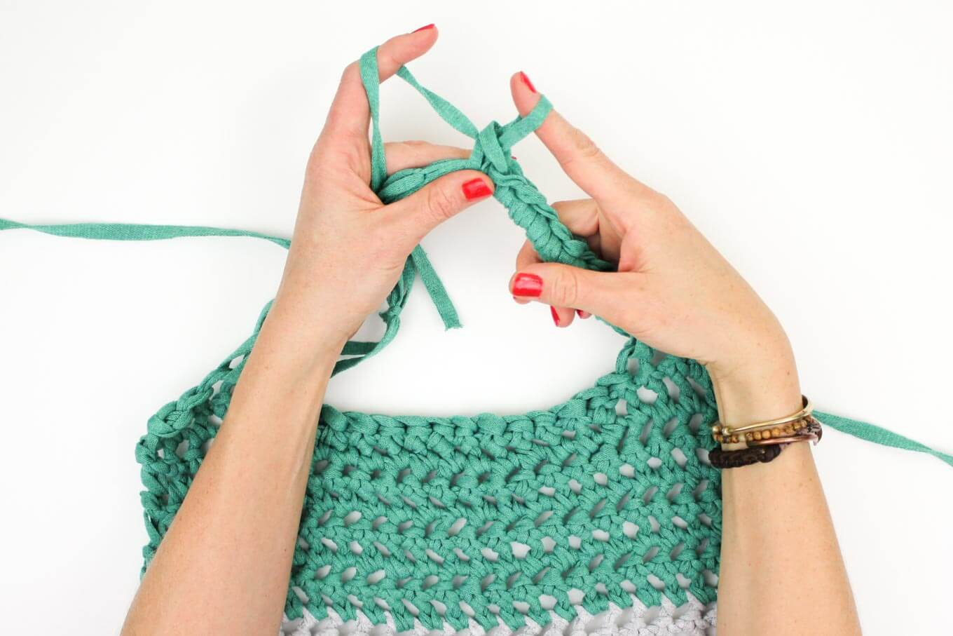 "This free market tote pattern and video tutorial is the perfect introduction on how to finger crochet! A speedy, satisfying project for adults and kids alike. Made using Lion Brand's Fast-Track yarn in ""Chopper Grey"" and ""Go Kart Green."" 