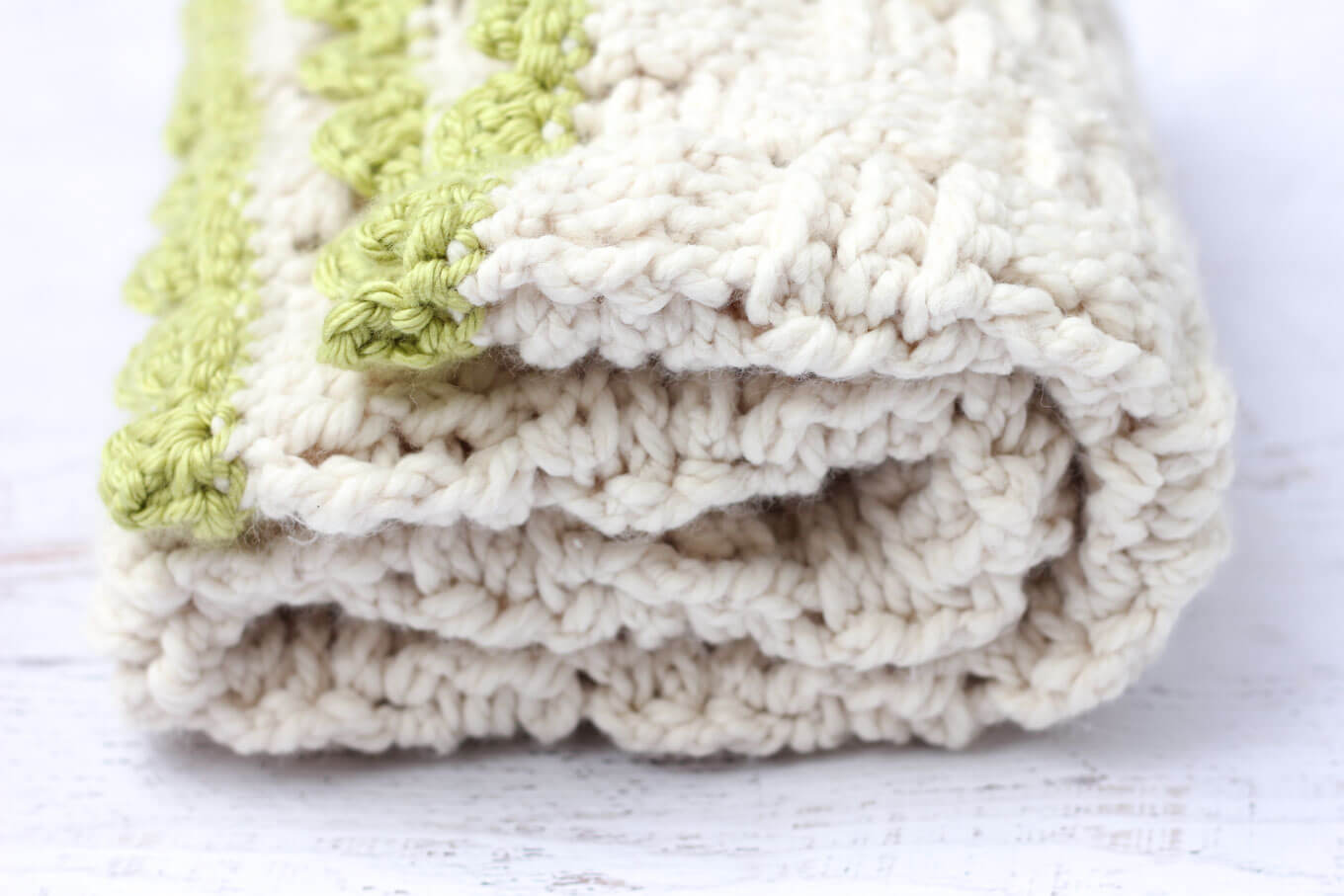 "Squishy yarn heaven! This free crochet basketweave blanket pattern is blooming with texture and makes a perfect lapghan-sized afghan. Made with Lion Brand Wool-Ease Thick & Quick in ""Fisherman"" and Hometown USA in ""Monteray Bay."" 