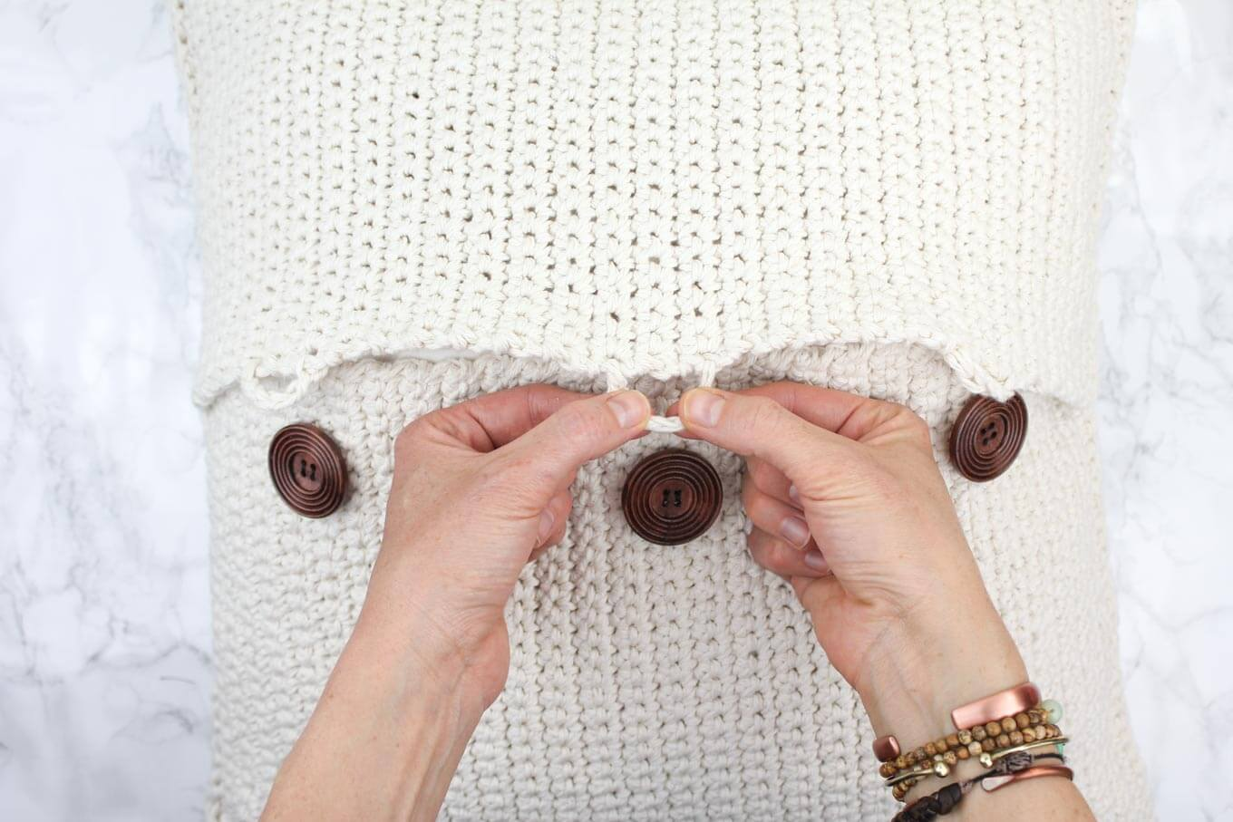 "Free crochet pillow pattern with button closures. Great beginner pattern made with Lion Brand Kitchen Cotton in ""Vanilla."""