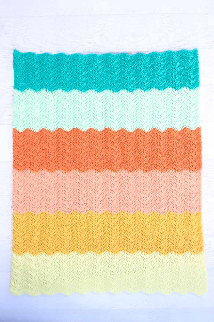 Pretty! Free modern gender neutral crochet baby blanket pattern using Lion Brand Baby Soft yarn in Lemon Drop, Pastel Yellow, Creamsicle, Apricot, Mint and Teal.