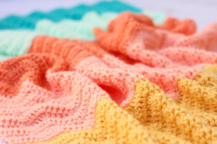Every new baby deserves a warm welcome into the world and this easy crochet baby blanket pattern puts a modern twist on the traditional ripple. Made using Lion Brand's Baby Soft yarn.