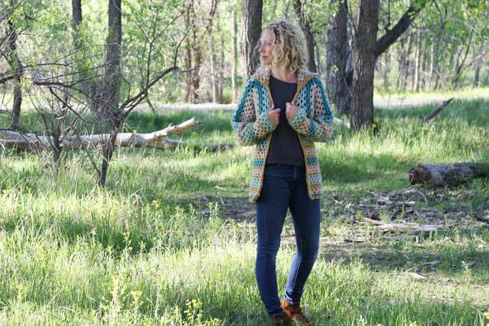 "Believe it or not, two simple granny hexagons are the foundation of this free crochet hexagon sweater pattern. ""The Campfire Cardigan"" is made with Lion Brand New Basic 175 in Juniper, Cafe Au Lait, Thyme and Camel. Woman wearing modern crochet sweater in the forest."
