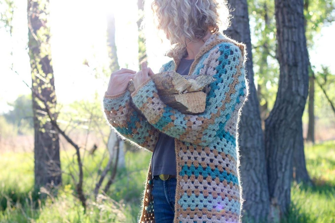 Blonde woman carrying firewood in the woods, wearing a crochet cardigan made from hexagons.