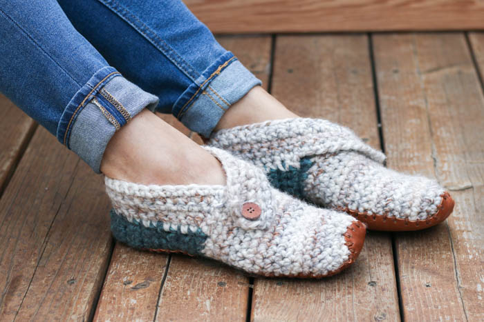 "This free crochet slippers pattern will satisfy the modern minimalist in you while also making you feel like a gift giving hero. They make the perfect gift for teachers, new moms, a friend who is sick and anyone else you want to wrap up in a little bit of love. Free women's slipper pattern from MakeAndDoCrew.com using Lion Brand Wool Ease Thick and Quick in ""Fossil"" and ""Blueberry."""