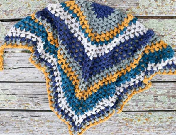 This crochet triangle scarf looks like the granny or bobble stitch, but it's actually the bead stitch. Free pattern and video tutorial!