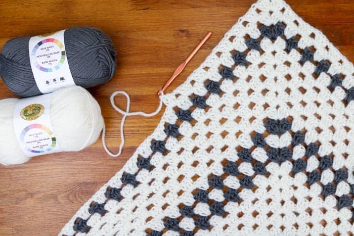 Lion Brand New Basic 175 yarn working a granny stitch wrap pattern.