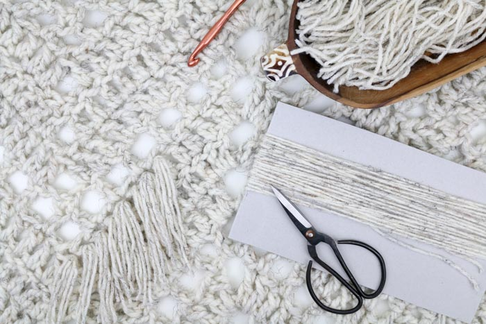"How to add fringe to a crochet or knit blanket pattern. Yarn pictured is Lion Brand Wool-Ease in ""wheat."""