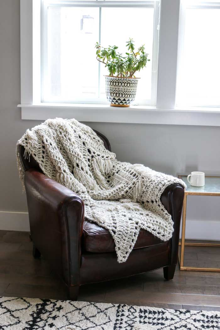Monochromatic doesn't have to be boring! In this modern fringed crochet blanket free pattern, two weights of Lion Brand Wool-Ease yarn combine to add instant style and texture to any room of your house.