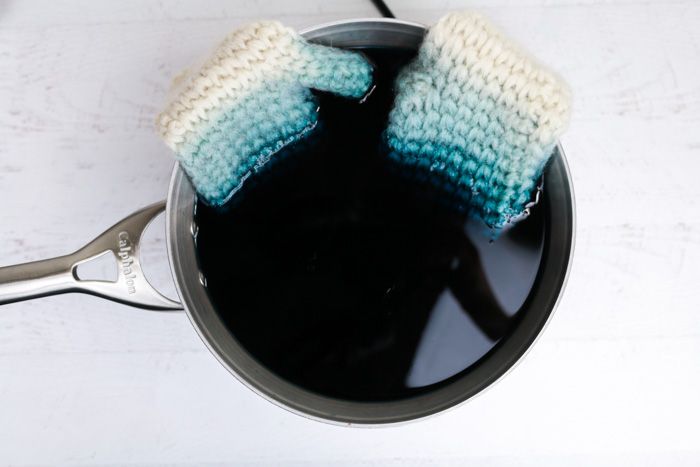 Learn an inexpensive trick to making any colored wool yarn you can imagine by using food coloring and vinegar for dye! Crochet mittens soaking in a dye bath.