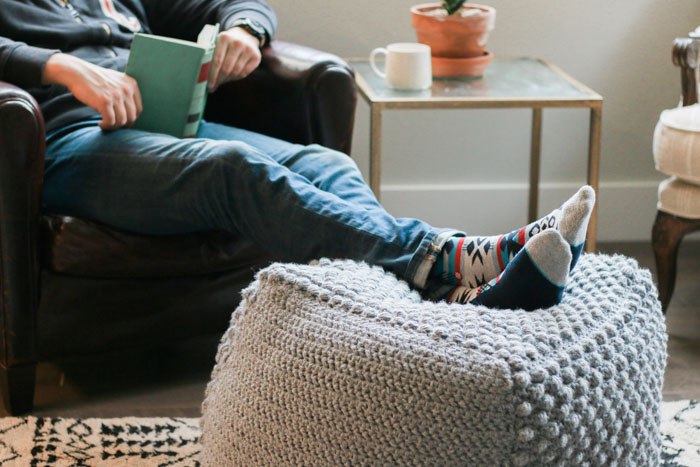This free crochet pouf pattern makes an excellent foot stool or ottoman. Made with Lion Brand Pound of Love yarn in Oxford Grey. Free bean bag pattern from Make & Do Crew.