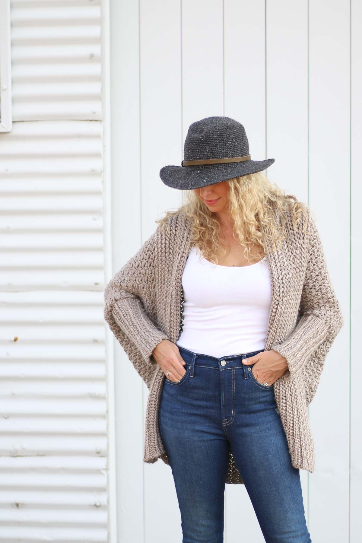A blonde woman wearing an oversized, baggy modern crochet cardigan. This free crochet cardigan pattern is very easy thanks to the sweater being crocheted from a simple rectangle.