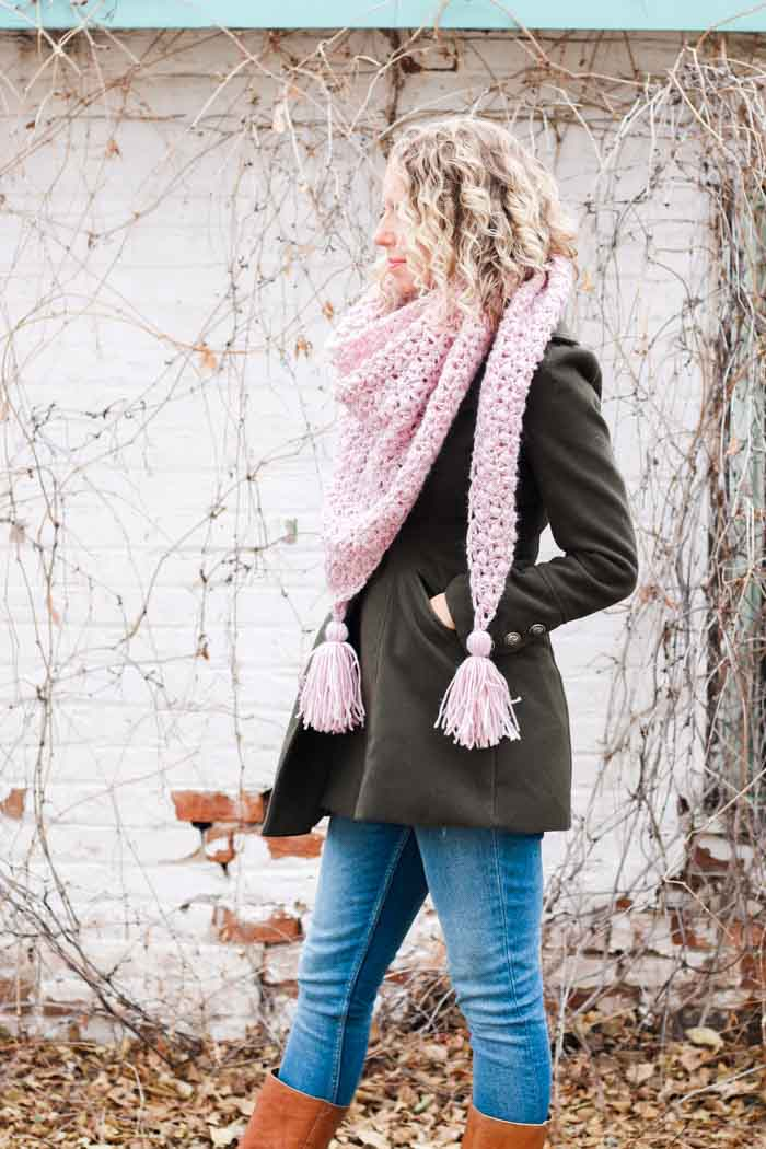 Woman wearing modern crochet triangle scarf with tassels. Free crochet pattern featuring Lion Brand Touch of Alpaca yarn.