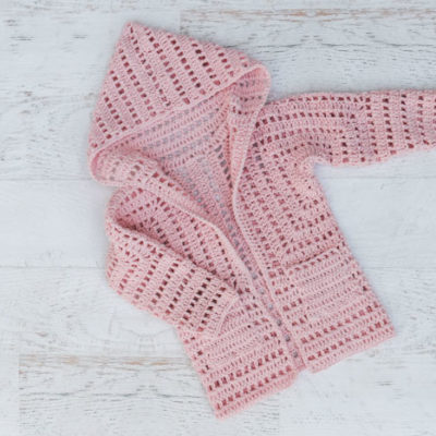Child's crochet cardigan made from two hexagons. Free sweater pattern for girls features lace eyelets in pink Lion Brand Touch of Butta yarn.