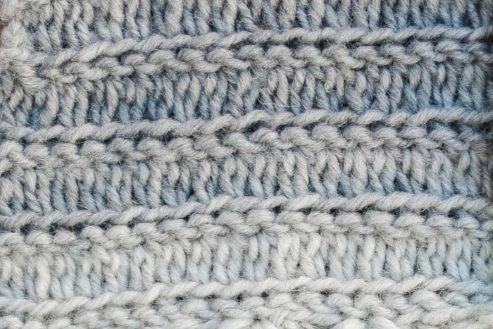 Closeup of a crochet stitch that looks knit worked in Lion Brand Scarfie yarn. Free pattern and crochet stitch video tutorial.