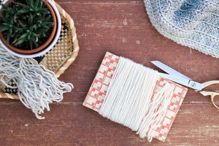 How to cut fringe for a crochet project by wrapping yarn around a book.