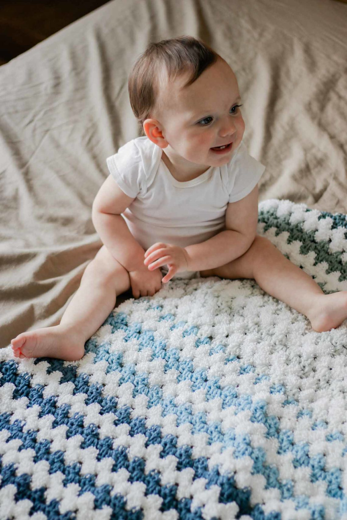 Cute baby sitting atop a gender-neutral, easy crochet granny stitch blanket pattern made with Lion Brand Mandala yarn.